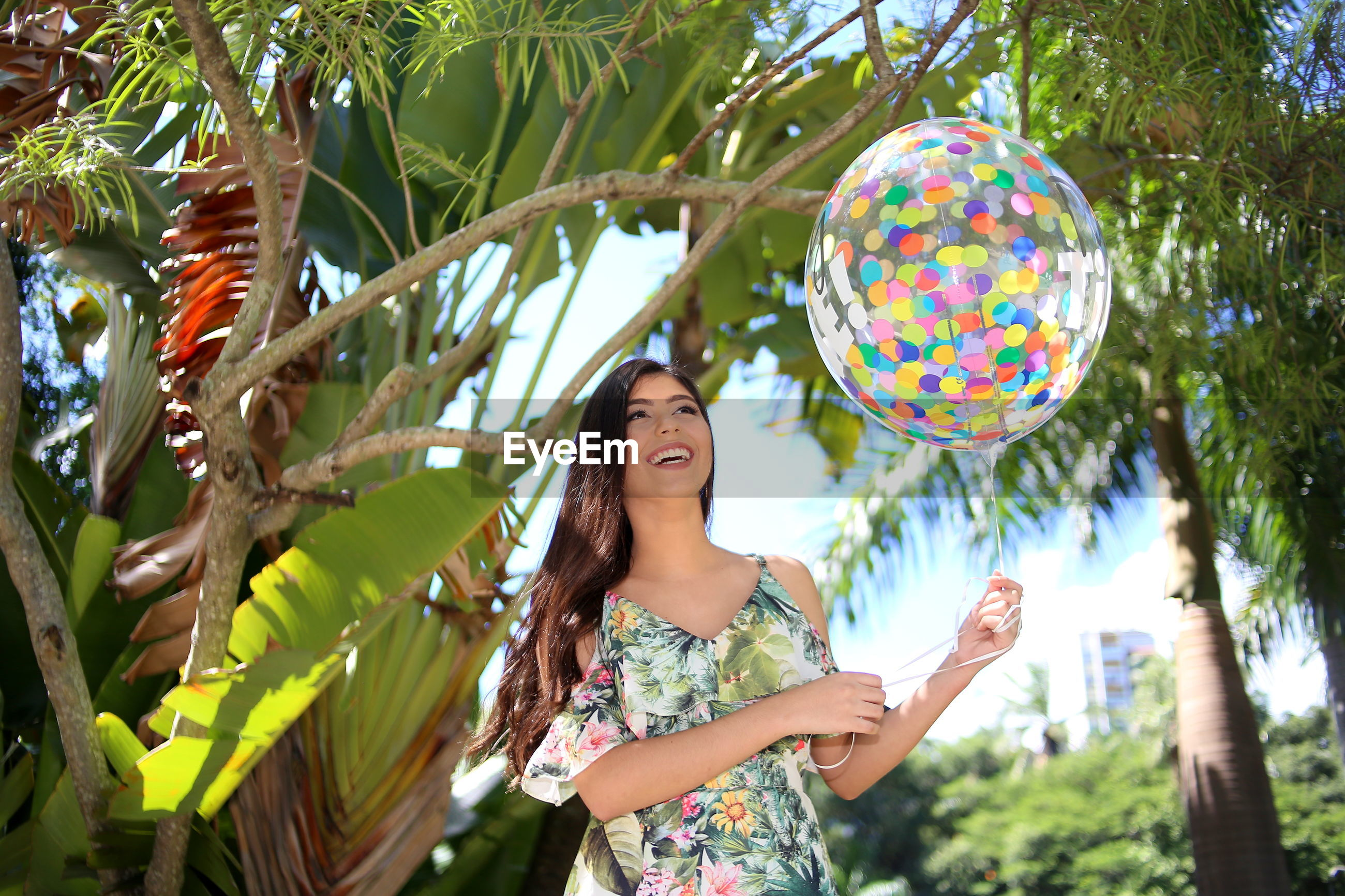 Low angle view of beautiful woman holding colorful balloon while standing against trees in park