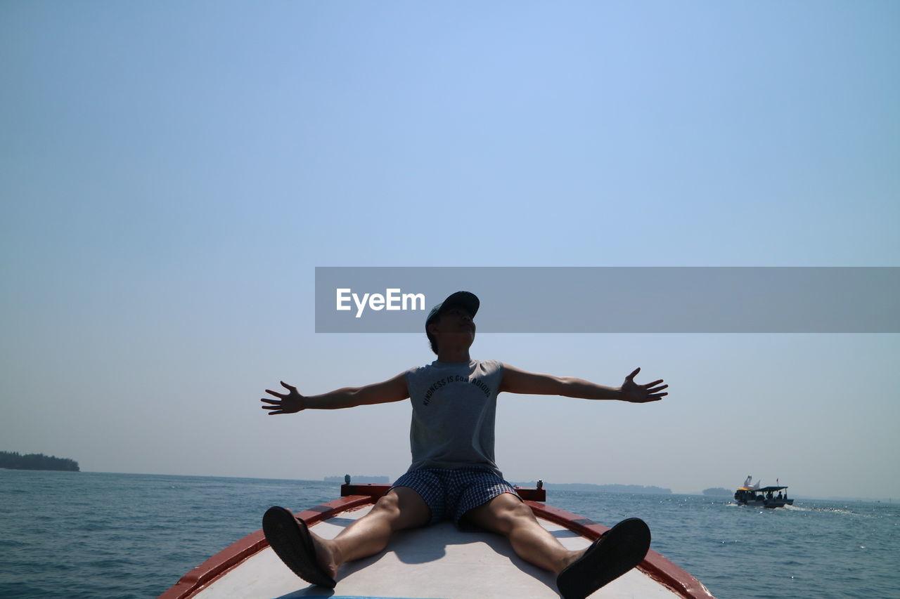 MAN SITTING ON SEA AGAINST CLEAR SKY