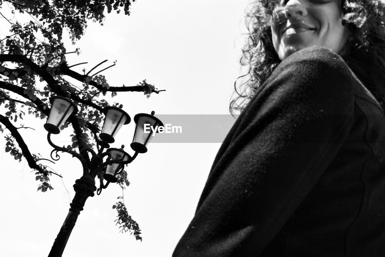 one person, real people, low angle view, tree, plant, lifestyles, sky, leisure activity, nature, women, lighting equipment, day, young adult, clear sky, outdoors, casual clothing, adult, side view, smiling, hairstyle