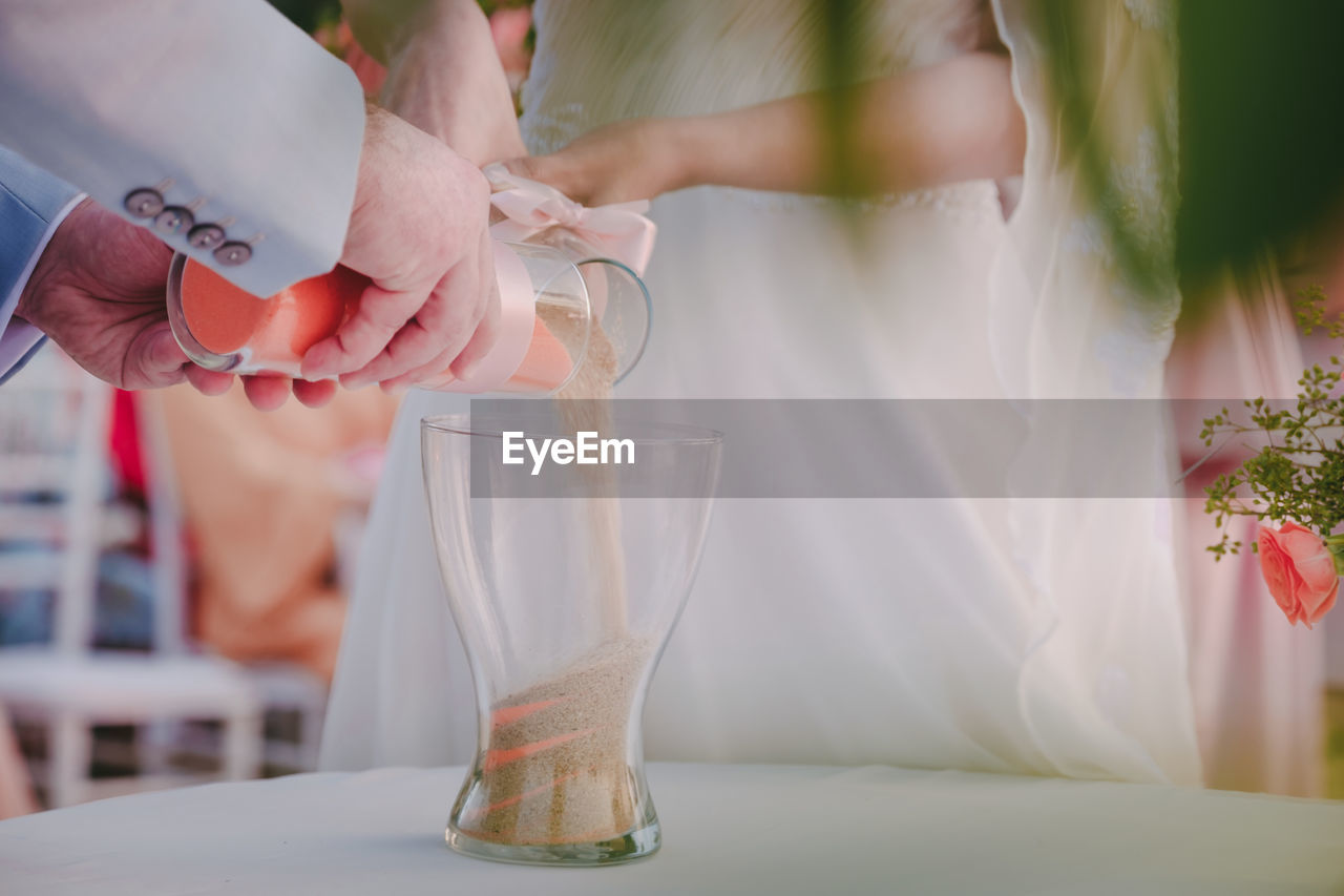 Midsection of bride and bridegroom pouring grain in glass on table