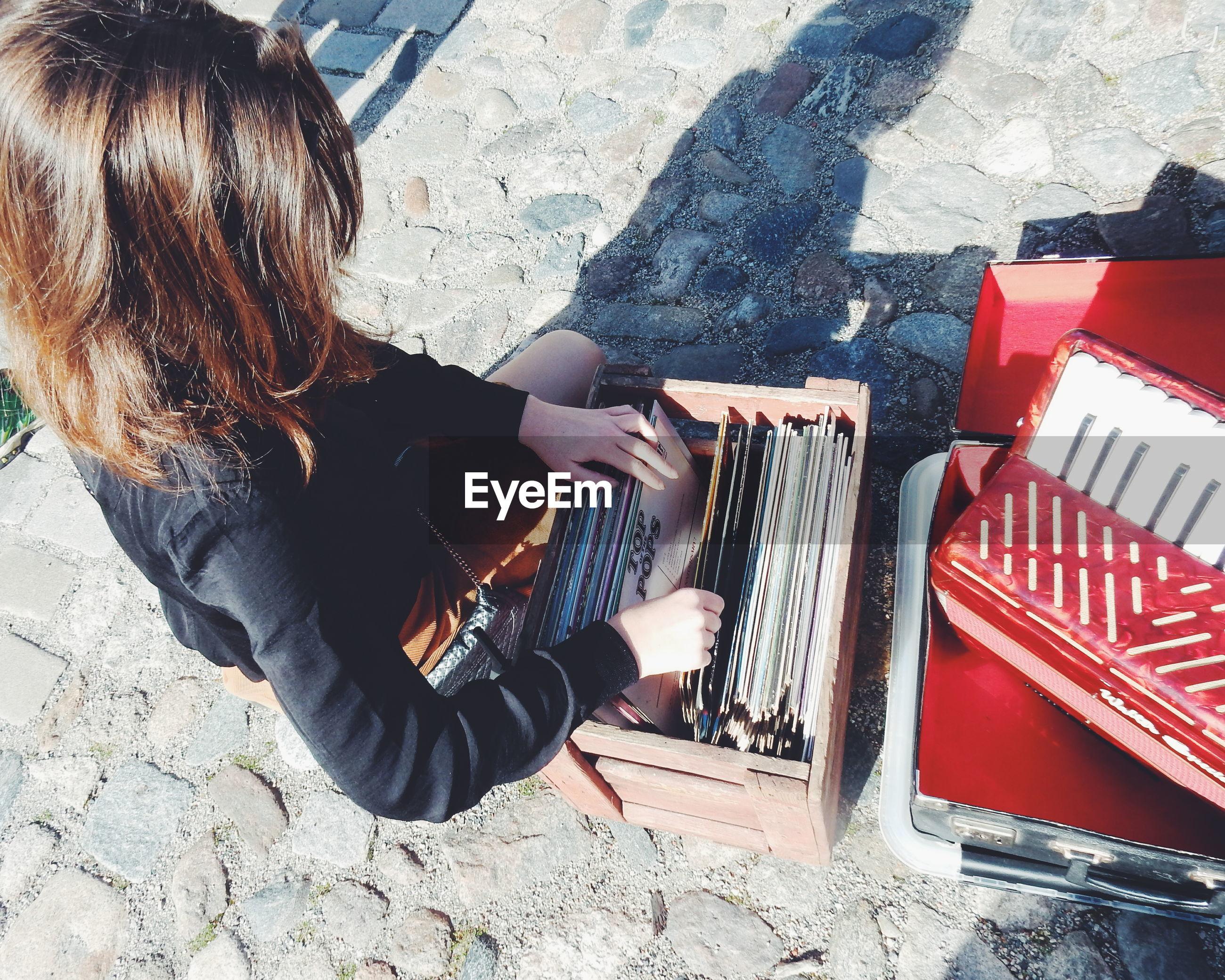 High angle view of woman choosing vinyl records at market