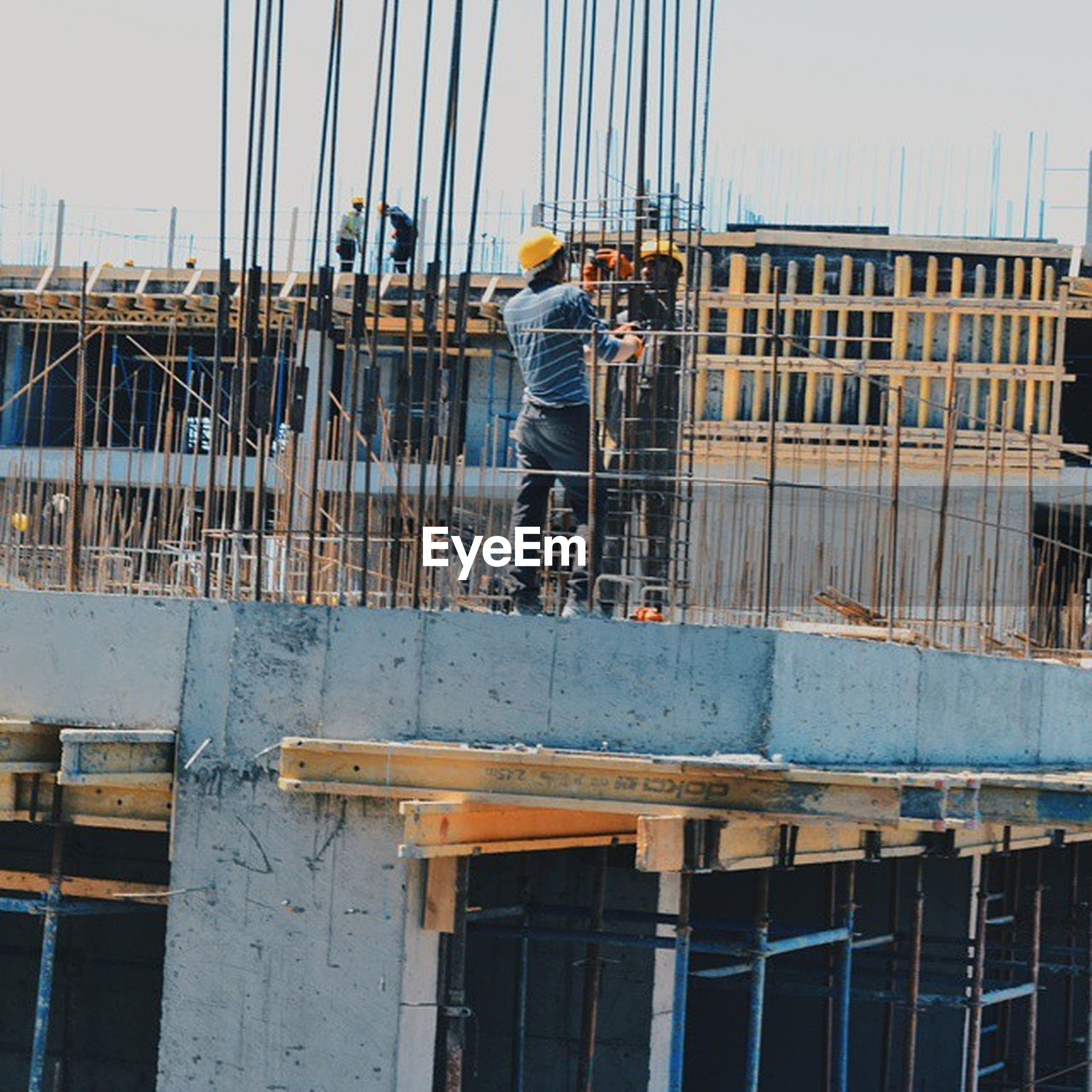 built structure, architecture, building exterior, railing, construction site, men, nautical vessel, working, day, industry, outdoors, construction, clear sky, construction industry, lifestyles, sky, low angle view, metal