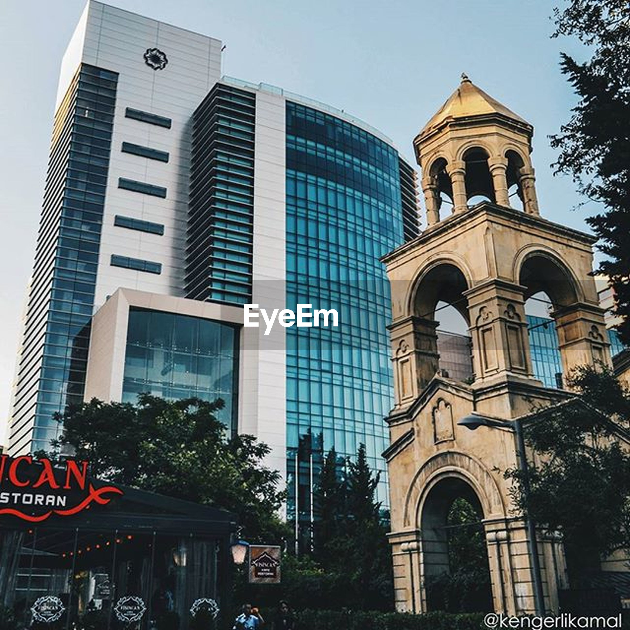 building exterior, architecture, built structure, low angle view, church, religion, tree, city, sky, facade, window, clock tower, tower, arch, clock, place of worship, day, outdoors