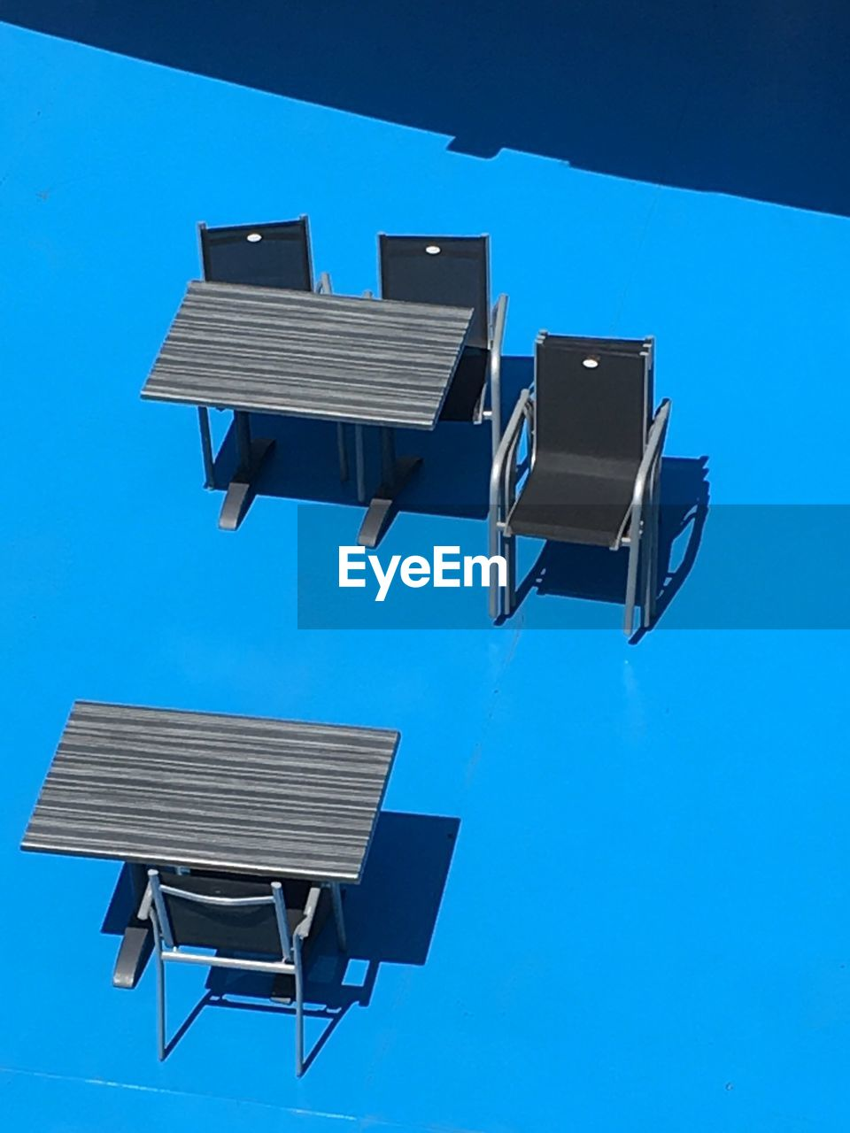 High angle view of empty tables and chairs on blue surface