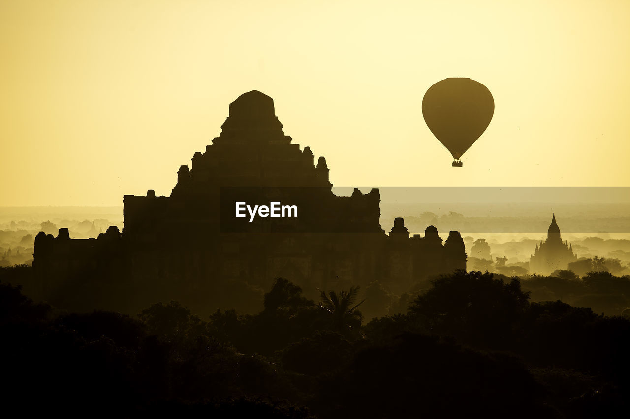 sky, architecture, building exterior, built structure, history, balloon, the past, place of worship, sunset, hot air balloon, travel destinations, no people, nature, belief, air vehicle, travel, silhouette, religion, tourism, outdoors, ancient civilization
