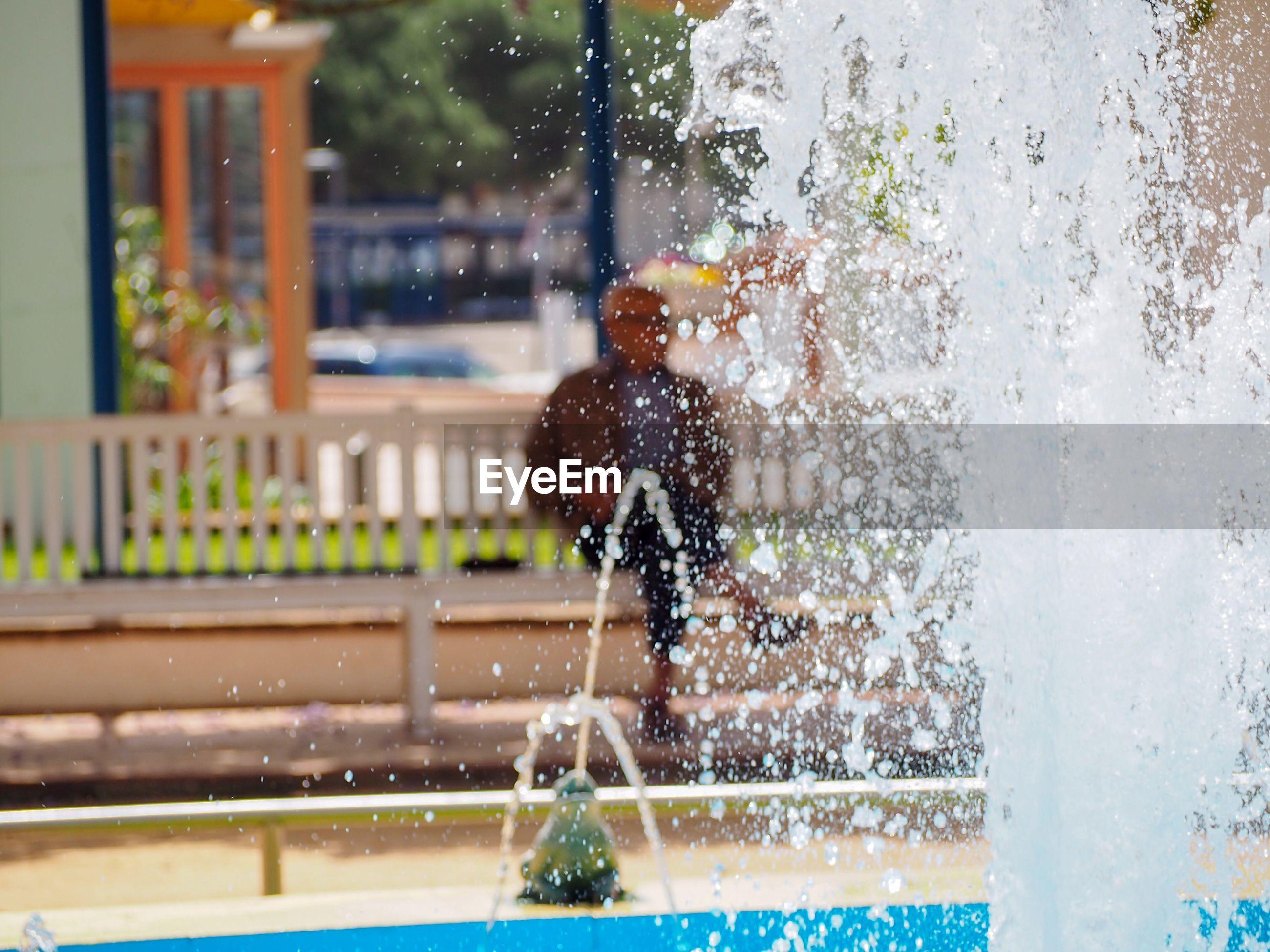 MAN SPLASHING WATER IN FOUNTAIN
