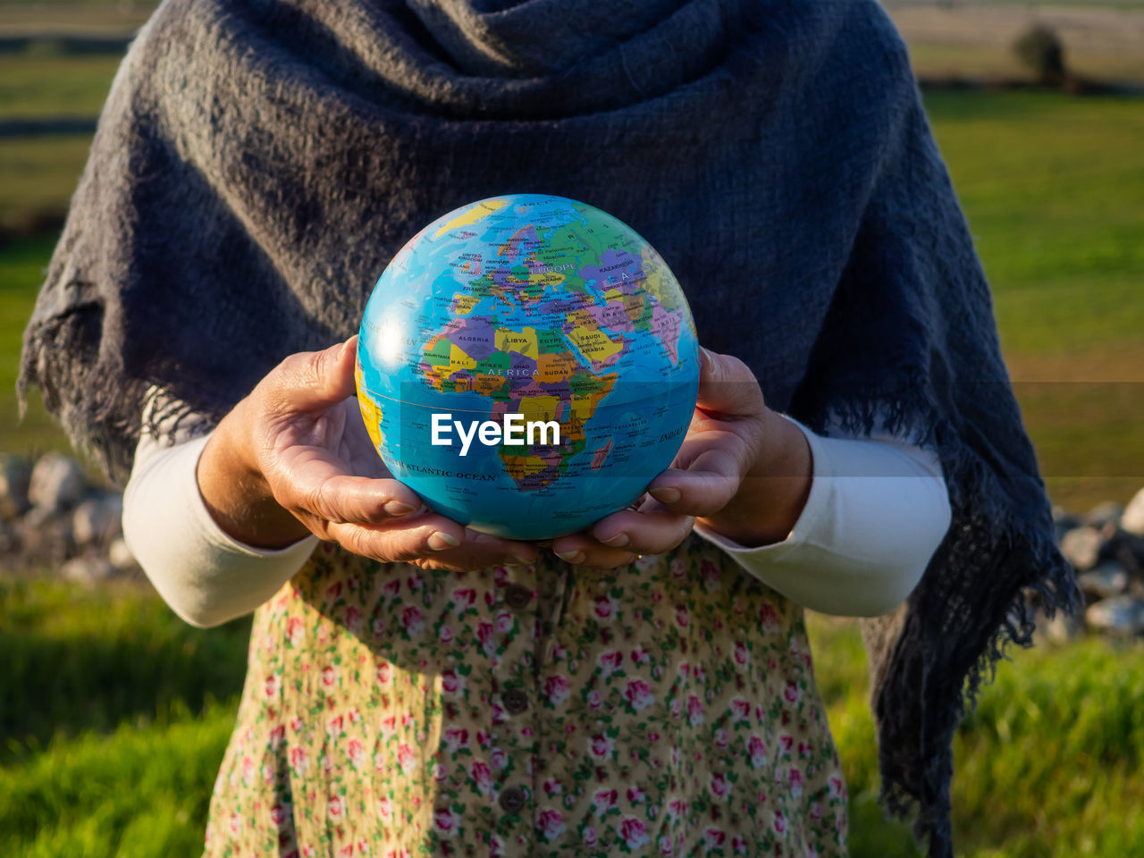 Midsection of woman holding globe while standing outdoors