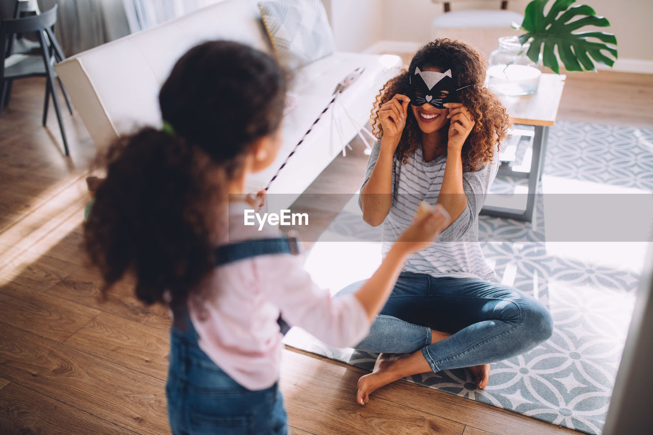 High angle view of mother and daughter playing with props at home