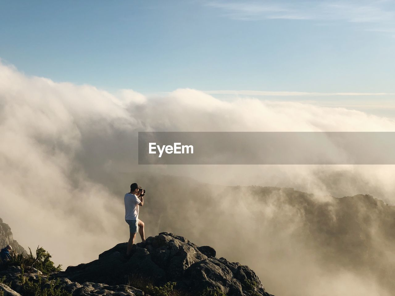 Full length of man photographing landscape against cloudy sky