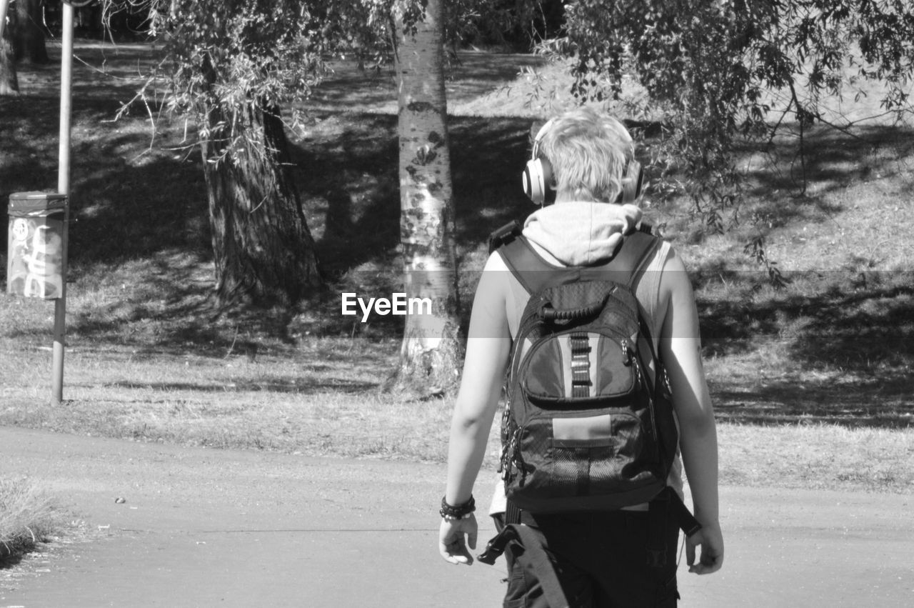 Rear view of backpack man walking on road during sunny day