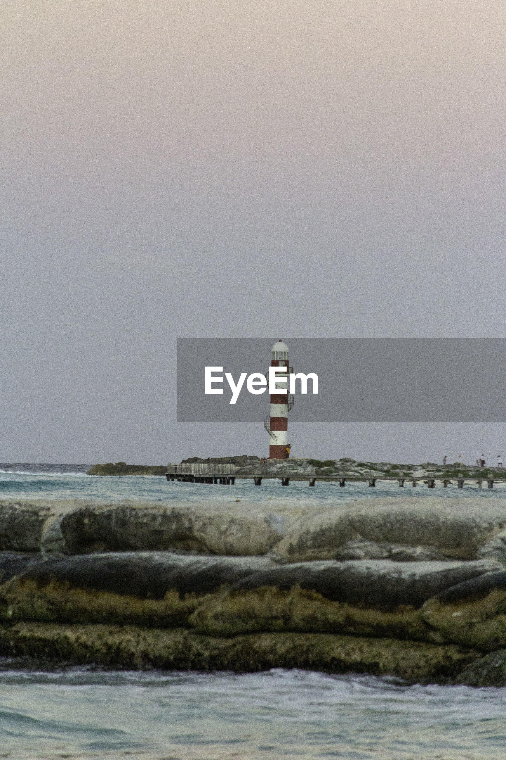 Lighthouse by sea against sky | ID: 139867099