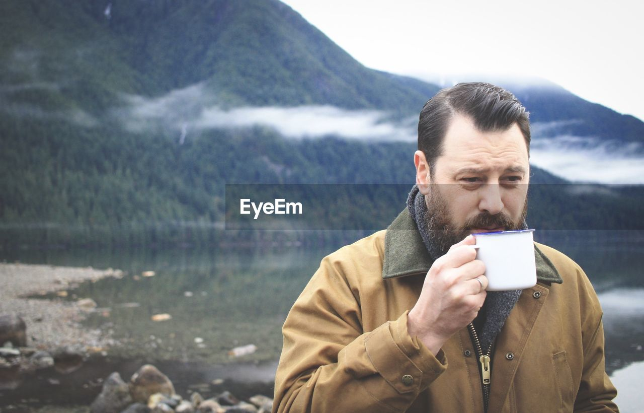 Man drinking coffee against lake and mountains
