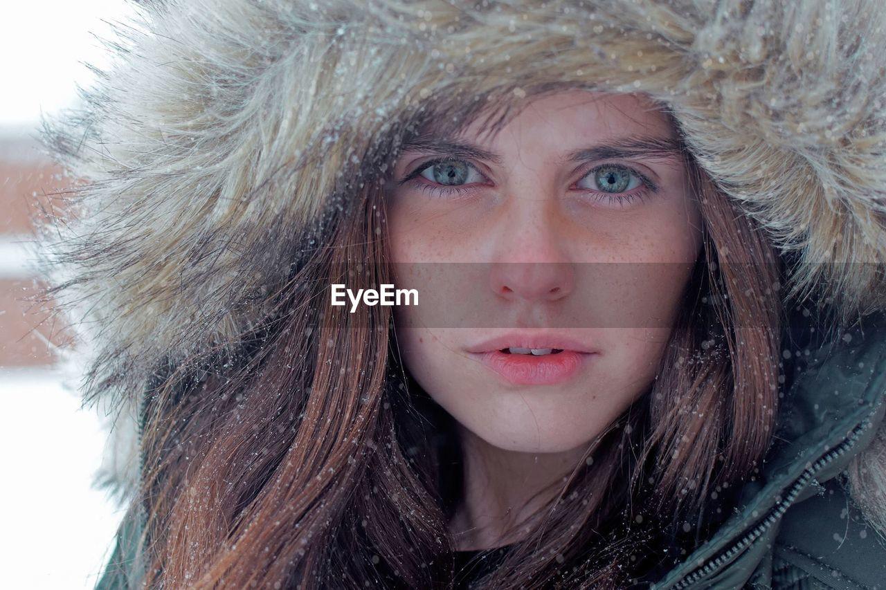 Close-Up Portrait Of Beautiful Woman Wearing Fur Coat During Snowfall