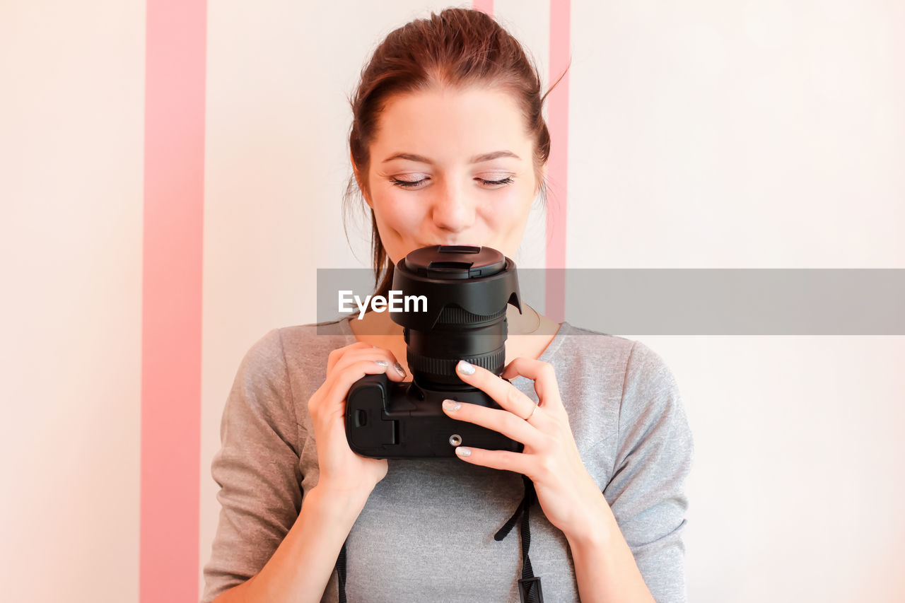 Portrait of smiling young woman holding camera against wall