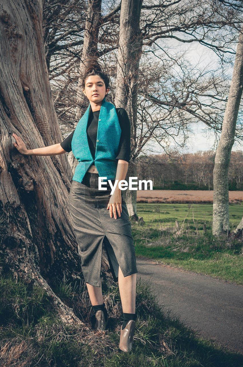tree, tree trunk, one person, full length, looking at camera, real people, portrait, front view, leisure activity, standing, bare tree, casual clothing, lifestyles, nature, outdoors, branch, young women, young adult, day, smiling, beautiful woman, happiness, people