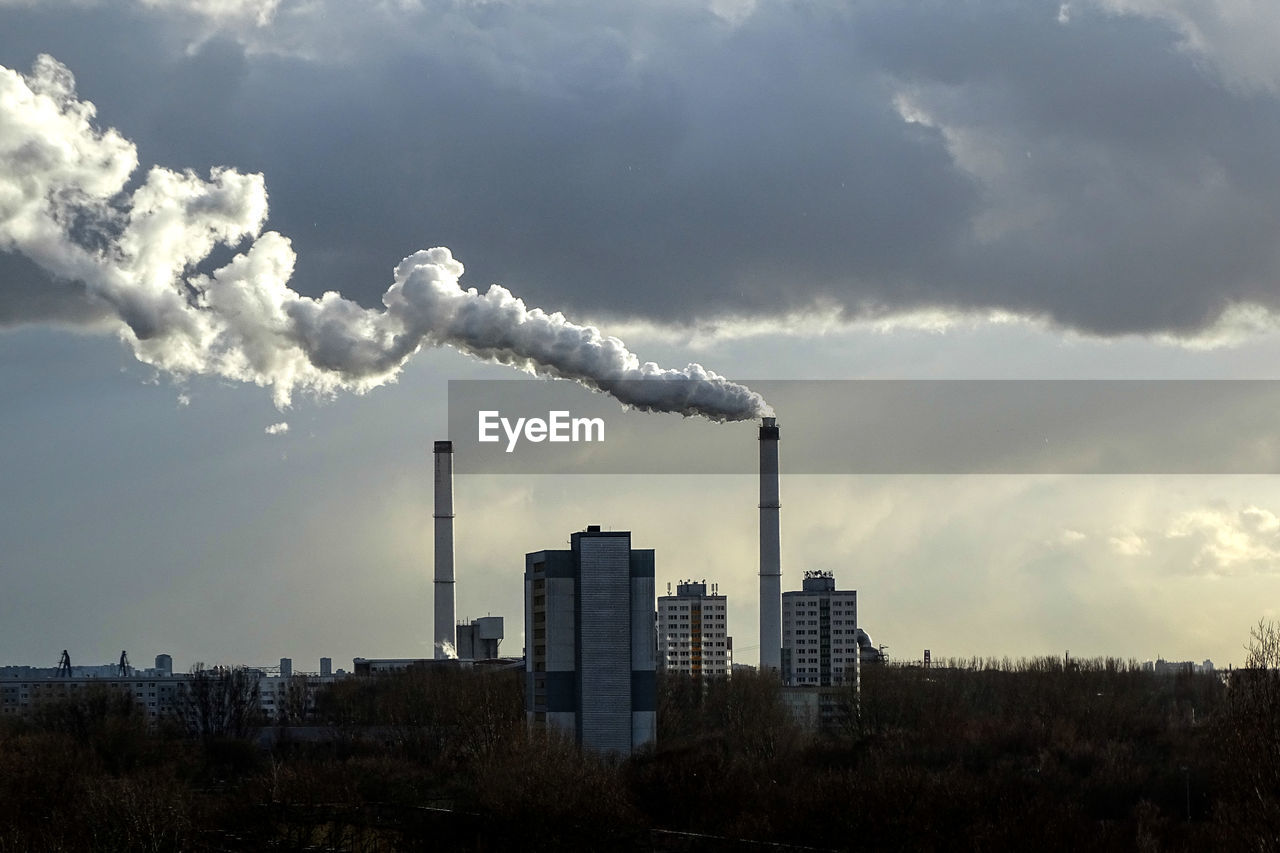 Distant Factory Emitting Smoke Against Cloudy Sky