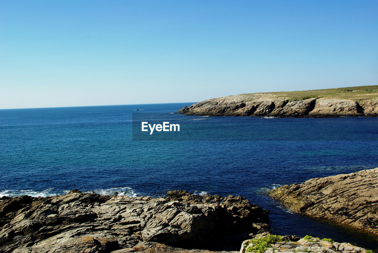 sea, water, horizon over water, nature, scenics, tranquil scene, clear sky, beauty in nature, tranquility, rock - object, blue, copy space, outdoors, idyllic, day, rippled, cliff, no people, sky, pebble beach