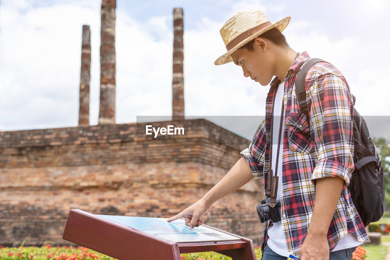 real people, one person, casual clothing, young adult, lifestyles, focus on foreground, hat, young men, day, side view, standing, nature, leisure activity, sky, architecture, built structure, checked pattern, holding, three quarter length, outdoors, hairstyle