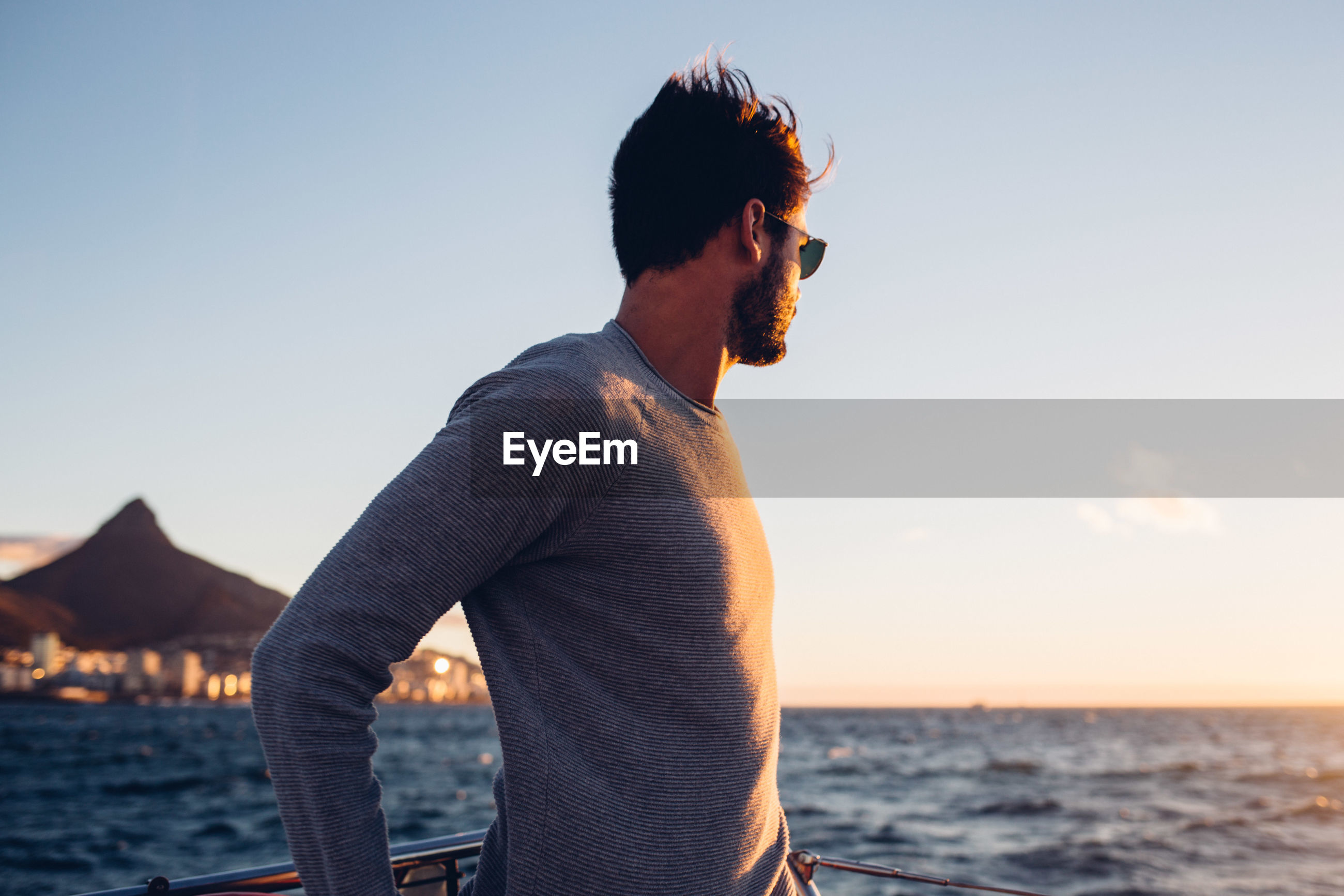 Young man standing in boat on sea against sky
