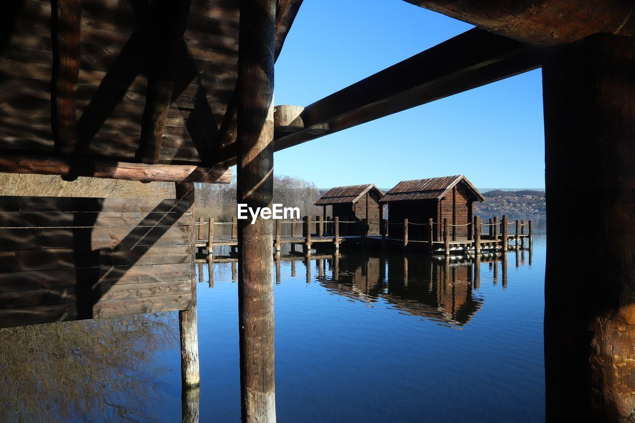 architecture, built structure, water, building, building exterior, no people, sky, wood - material, day, nature, reflection, house, waterfront, outdoors, lake, pier, sunlight, blue, old, architectural column, wooden post