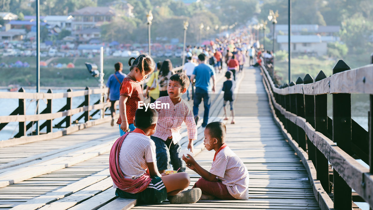 group of people, real people, men, railing, sitting, architecture, women, lifestyles, day, leisure activity, bridge, adult, wood - material, connection, people, built structure, pier, casual clothing, group, relaxation, bridge - man made structure, footbridge, outdoors