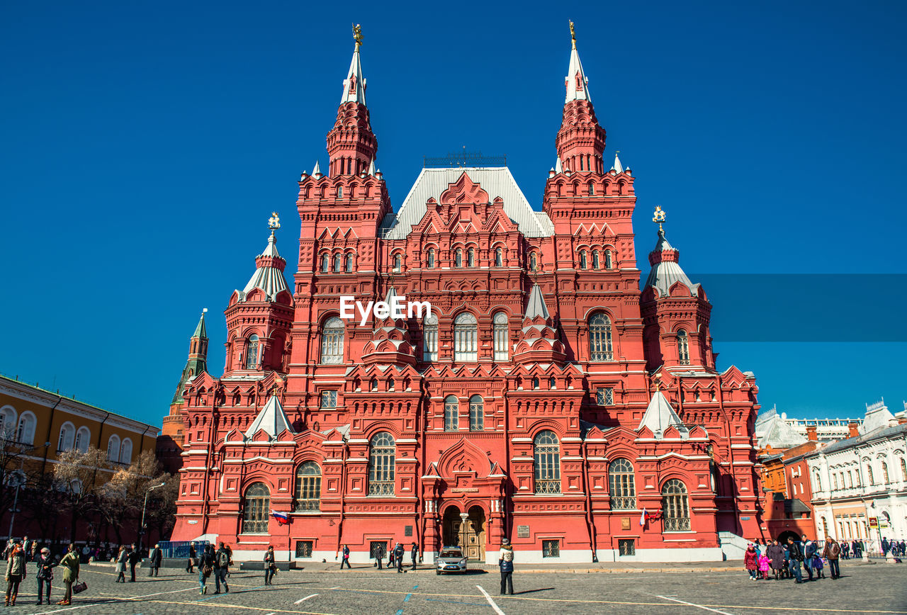 architecture, built structure, building exterior, clear sky, history, place of worship, real people, large group of people, travel destinations, religion, day, tourism, blue, outdoors, spirituality, leisure activity, men, women, sky, vacations, people