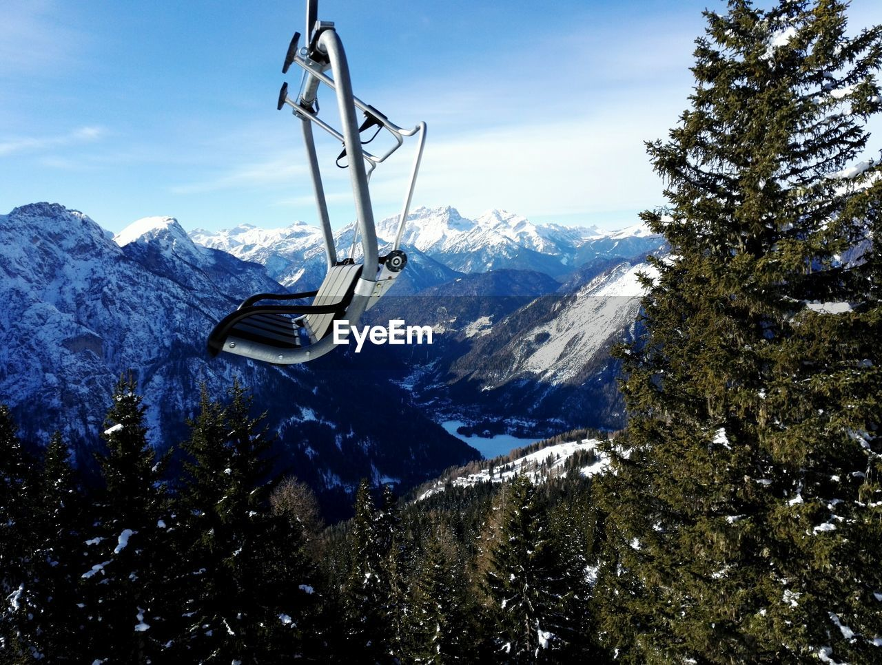 Ski Lift By Snow Covered Mountains Against Sky