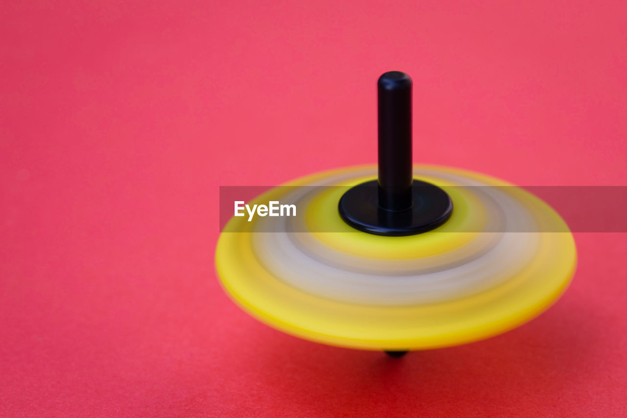 Close-up of spinning top over pink background