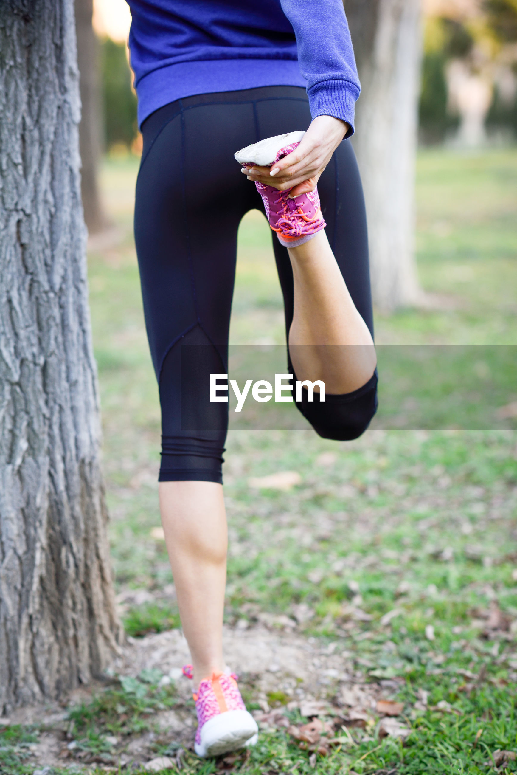 Low section of woman doing yoga by tree trunk