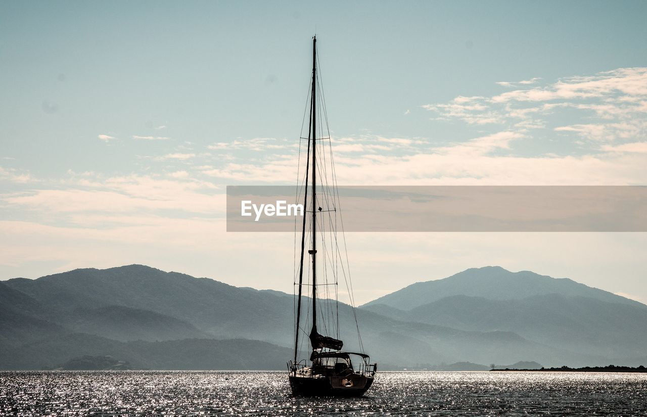 Sailboat On Sea Against Mountains