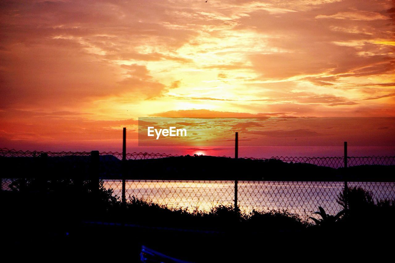 Scenic View Of Lake By Fence Against Orange Sky