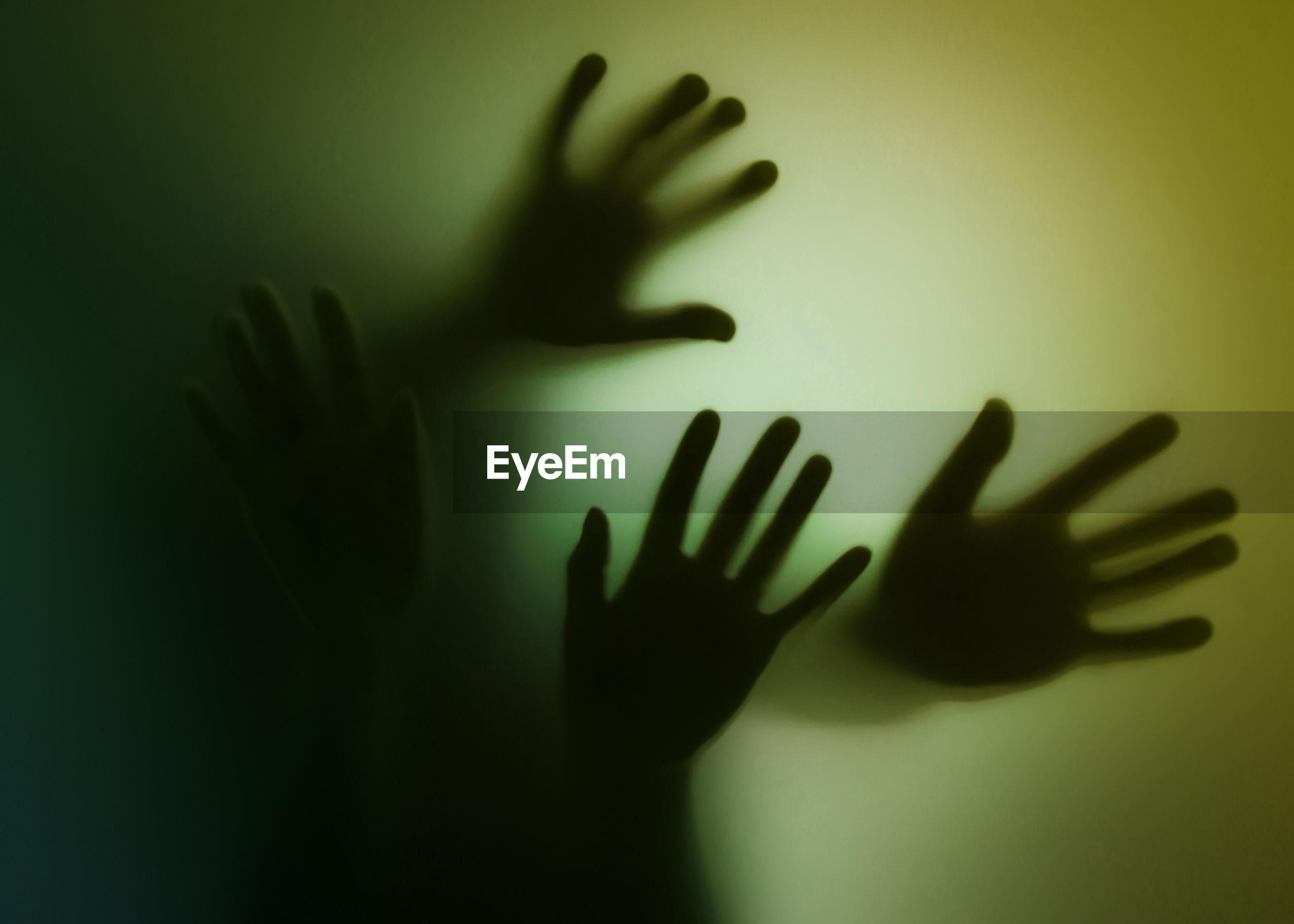 Hands seen through glass window