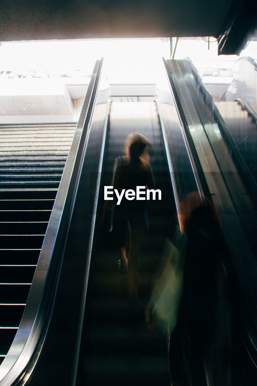 Blurred Motion Of People On Escalator