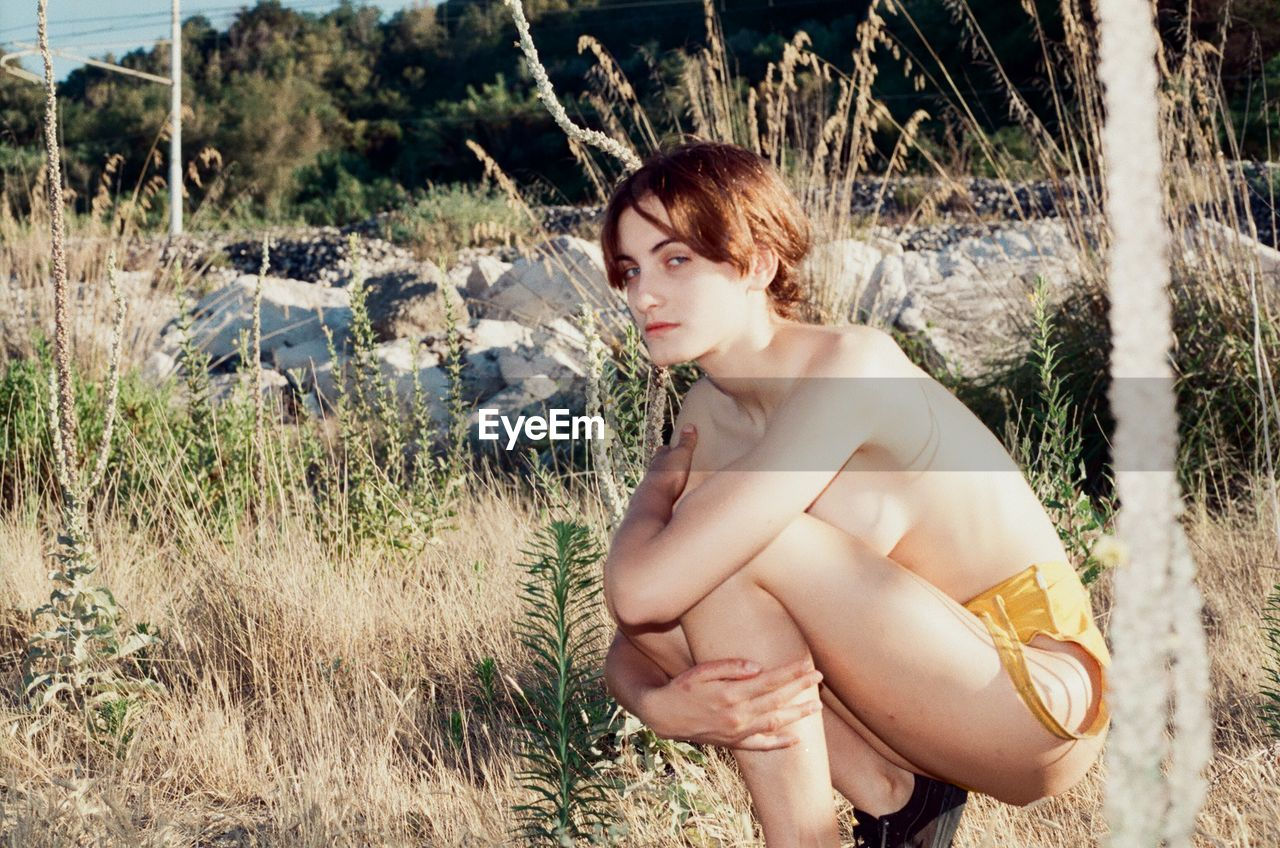 Shirtless Young Woman Crouching On Field