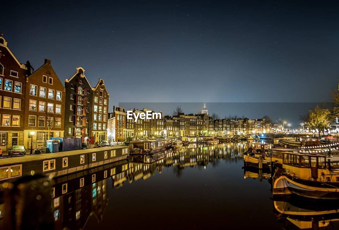 Boats Moored On Canal Amidst Illuminated Buildings At Night