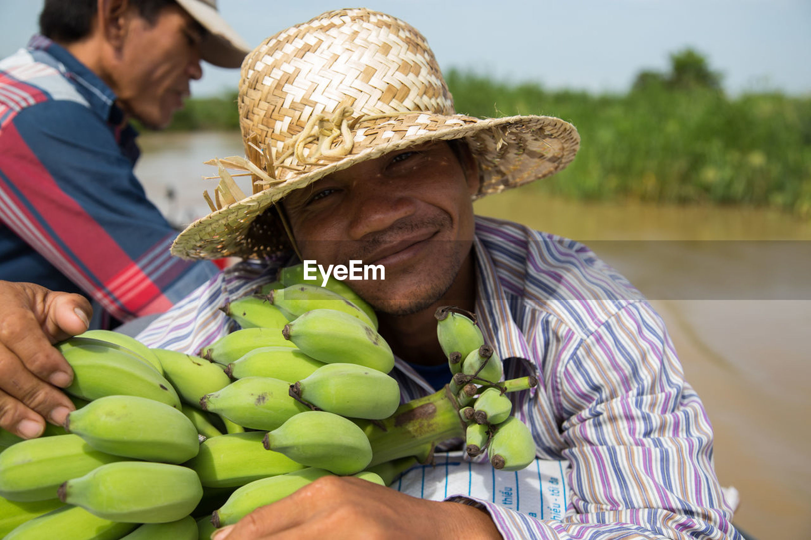 real people, hat, food and drink, fruit, outdoors, day, focus on foreground, men, freshness, healthy eating, food, mature men, two people, sitting, nature, close-up