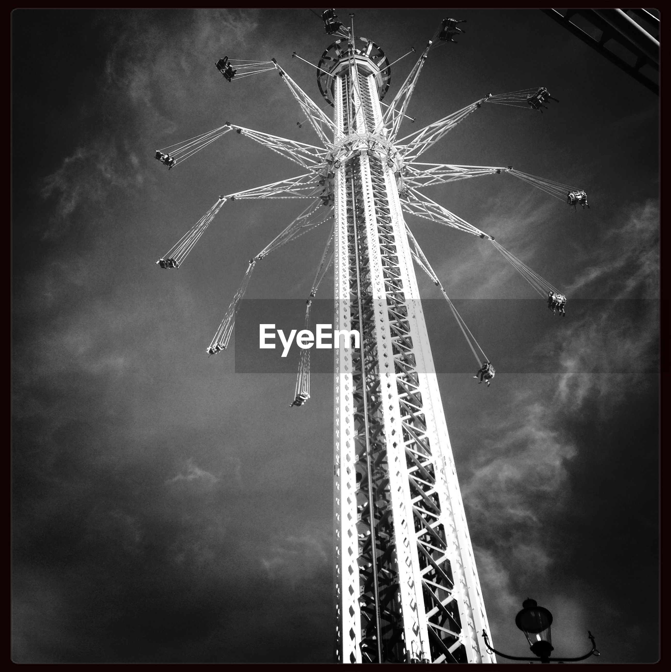 arts culture and entertainment, low angle view, sky, amusement park, amusement park ride, illuminated, transfer print, night, enjoyment, motion, fun, chain swing ride, celebration, auto post production filter, ferris wheel, leisure activity, event, cloud - sky, outdoors, firework display