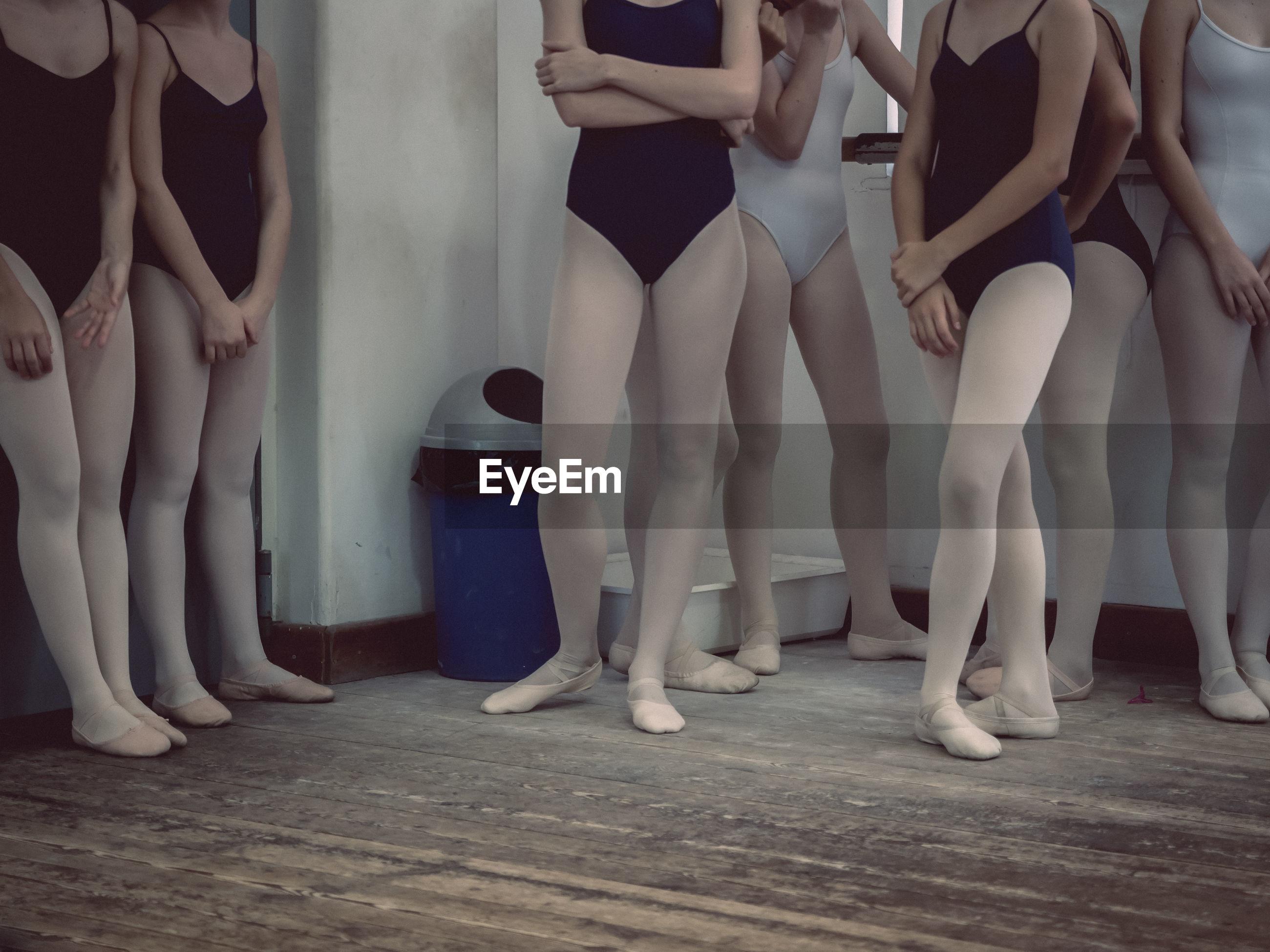 Low section of ballet dancers standing on wooden floor
