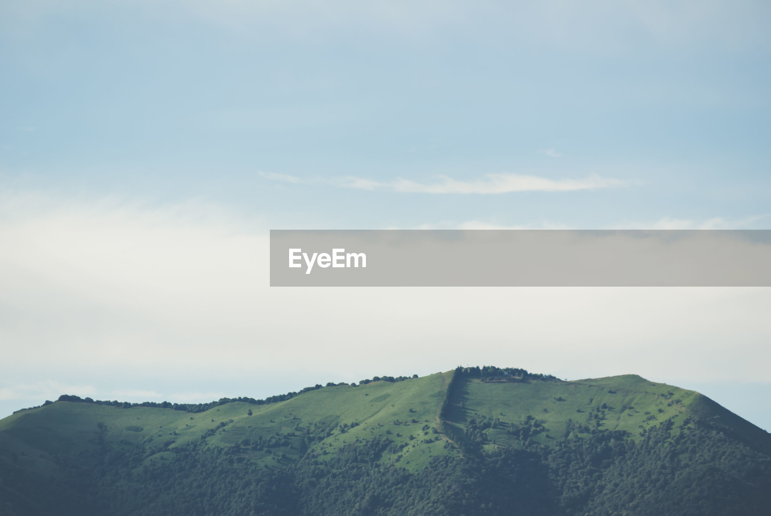 Scenic view of green mountain against sky