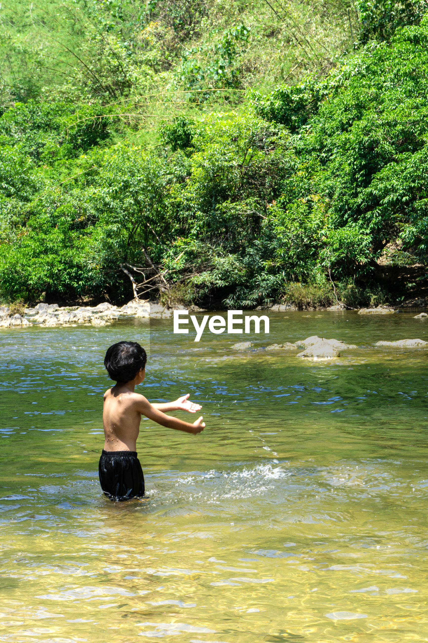Rear view of shirtless boy in river