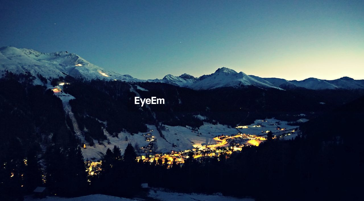Scenic view of snow covered mountains against clear sky at dusk