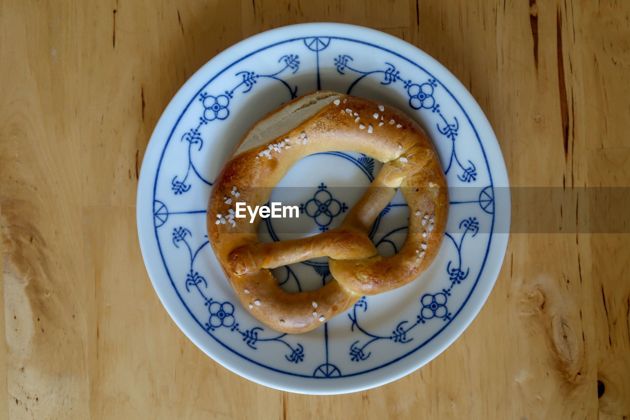 High angle view of pretzel in plate on wooden table