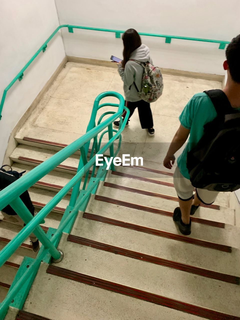 staircase, full length, railing, real people, leisure activity, steps and staircases, rear view, high angle view, lifestyles, women, people, architecture, casual clothing, men, walking, two people, adult, nature, togetherness, day