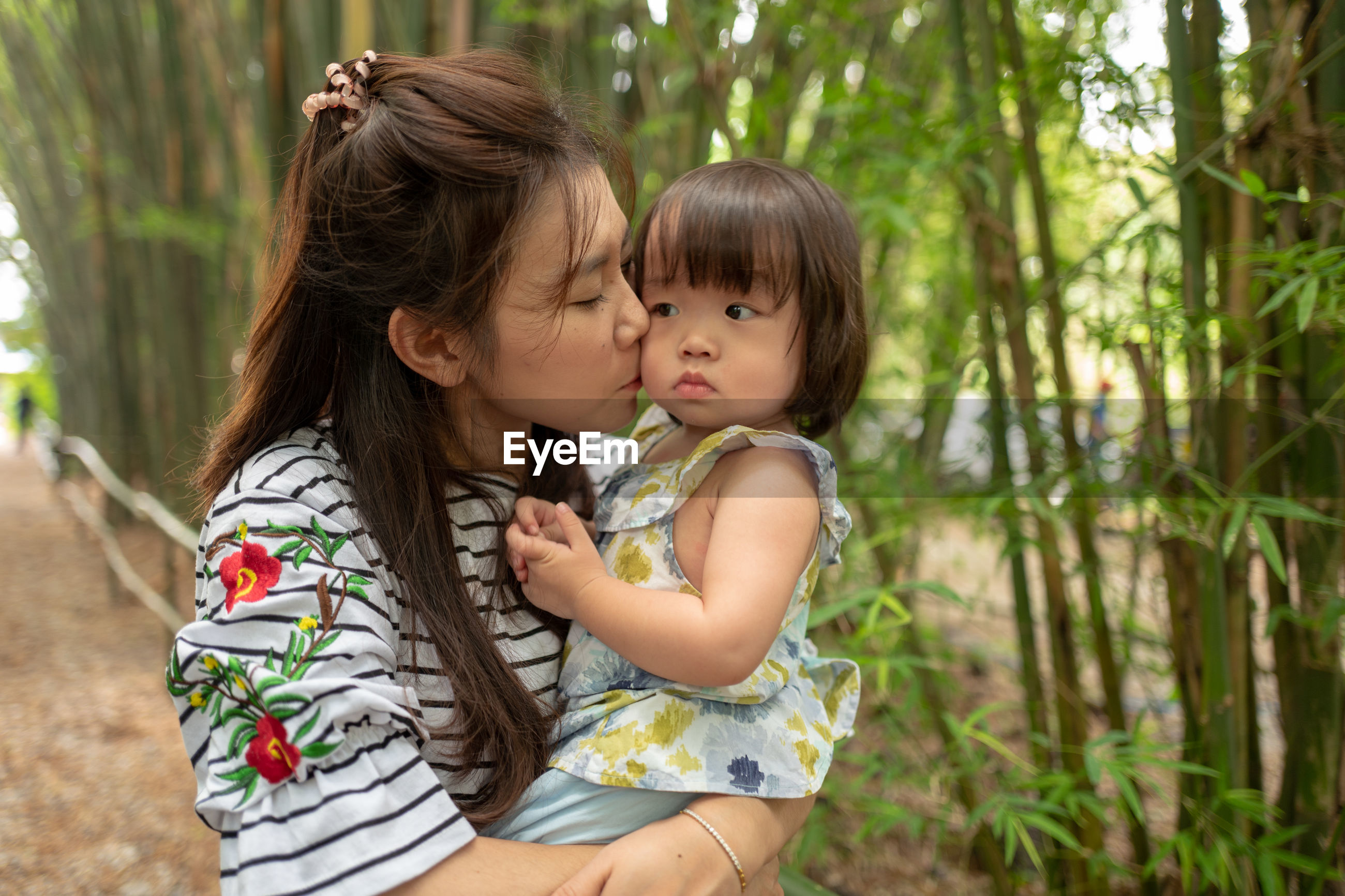 Mother kissing cute daughter