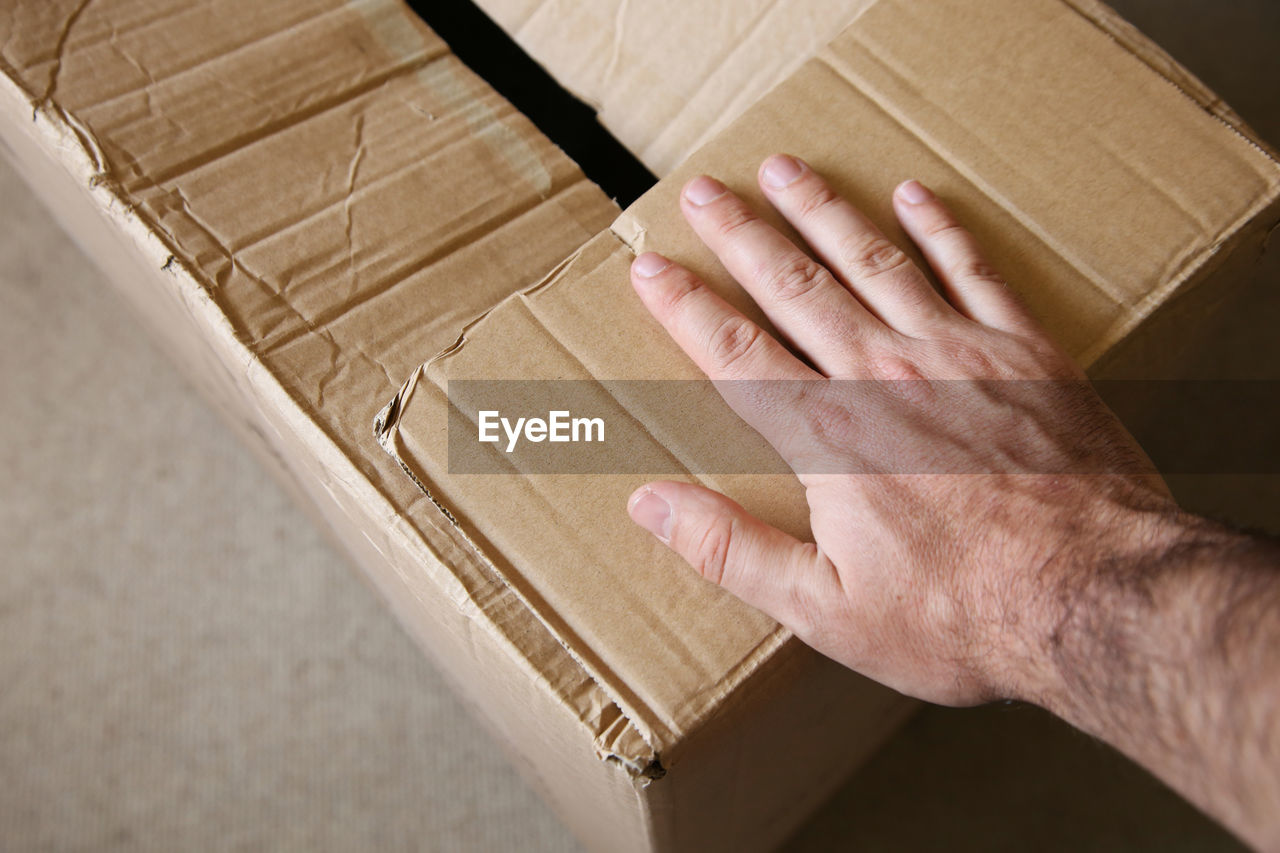 HIGH ANGLE VIEW OF PERSON HAND HOLDING BOX IN CRATE