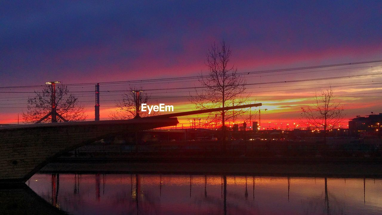 sunset, reflection, orange color, silhouette, sky, beauty in nature, nature, tree, water, no people, tranquil scene, scenics, cloud - sky, outdoors, sun, tranquility, built structure, architecture, electricity pylon, city