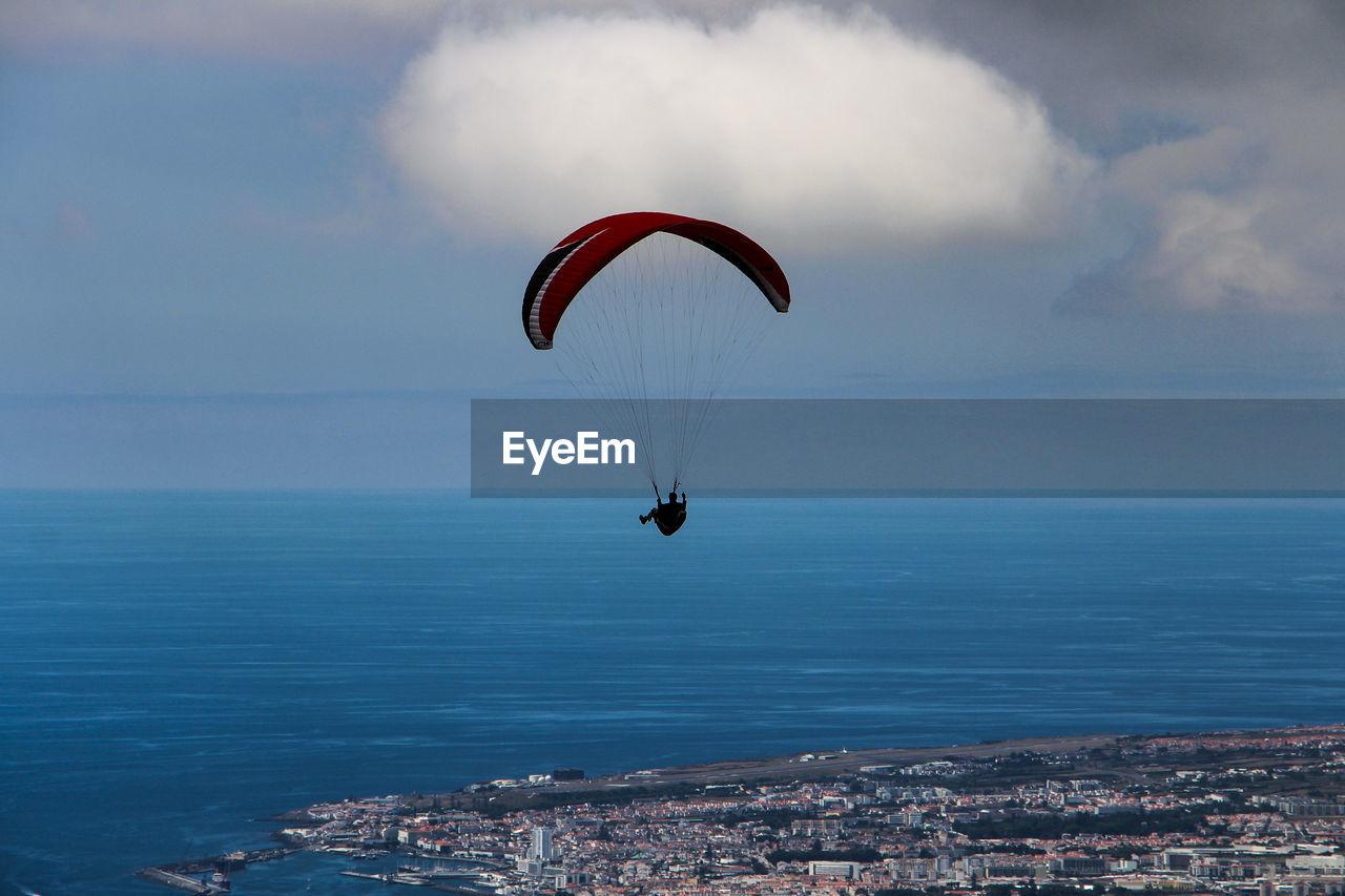 Man paragliding over sea