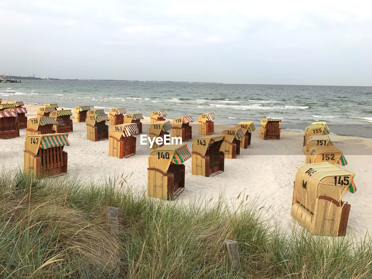 sea, land, sky, horizon, water, horizon over water, beach, scenics - nature, beauty in nature, nature, hooded beach chair, grass, cloud - sky, day, no people, tranquility, tranquil scene, non-urban scene, plant, outdoors, wooden post