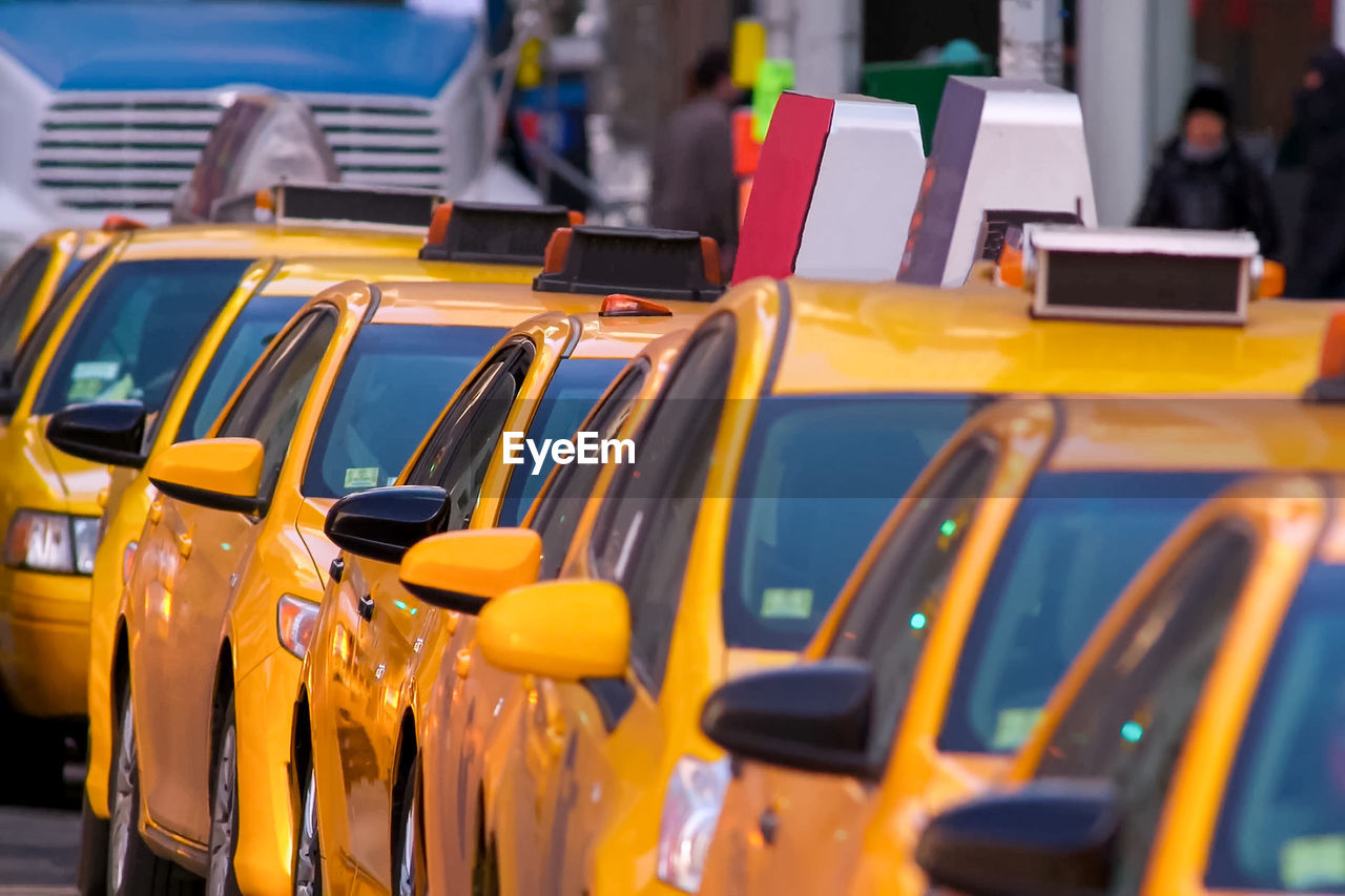 yellow, mode of transportation, car, transportation, taxi, land vehicle, in a row, city, day, yellow taxi, focus on foreground, incidental people, motor vehicle, bus, traffic, selective focus, outdoors, for sale, close-up