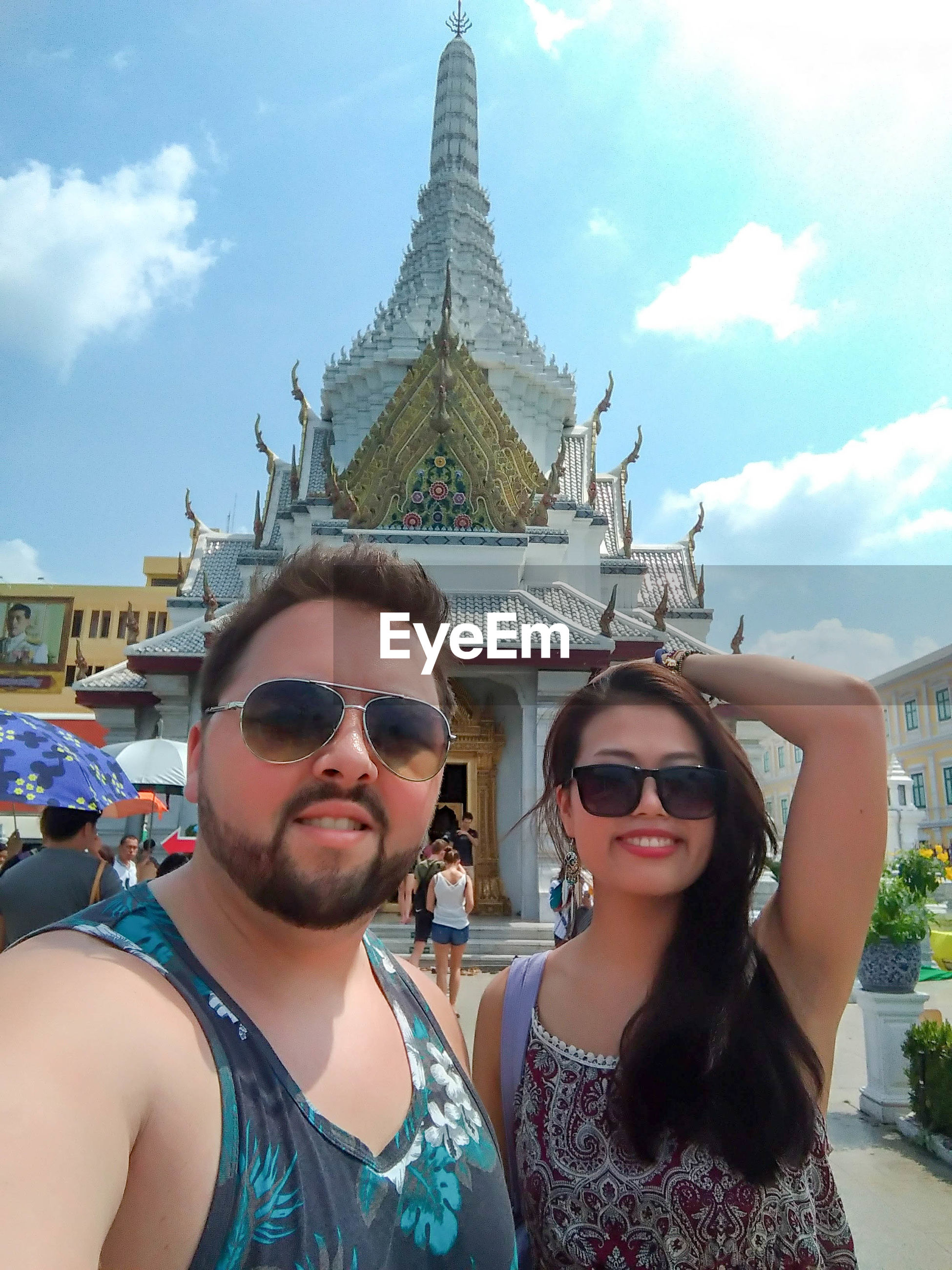 Portrait of couple wearing sunglasses while standing against temple